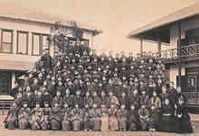 100名収容の新校舎の前で全員集合写真(1887年)1885年から生徒数がどれほど増えたかがわかる。前列右からホワイト、フーパー、第2列右からウェンライト、シェッド