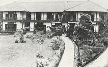 正面から見た同志社女学校校舎 白壁と濃褐色の木製ベランダが美しいコントラストをなしていた。前庭のアプローチもモダンである