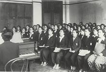 1944年 加藤テイ教授。「この年、市内の女専合唱祭があり、私達はハレルヤコーラスを歌った。髪はおかっぱは許されず、束ね髪。靴の入手は困難なため藁草履、モンペでした」(服部フジ子)