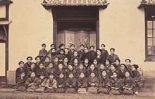 同志社女学校第1期隆盛期(1880年度)生徒全員集合写真 京都ホーム創立以来孤軍奮闘していたスタークウェザーにとって初めて女学校の陣容が整ったと感じられた年。上段2列目左から 宮川経輝(1人おいて)・スタークウェザー・山本佐久・パーミリー・デイヴィス夫人(ソフィア)・加藤勇次郎。生徒42名