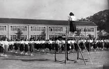 女専最後の運動会 新制女子大学と合同、今出川の大学グラウンド。開会礼拝(後の校舎は同工館、現博遠館の位置)(1950年11月3日)
